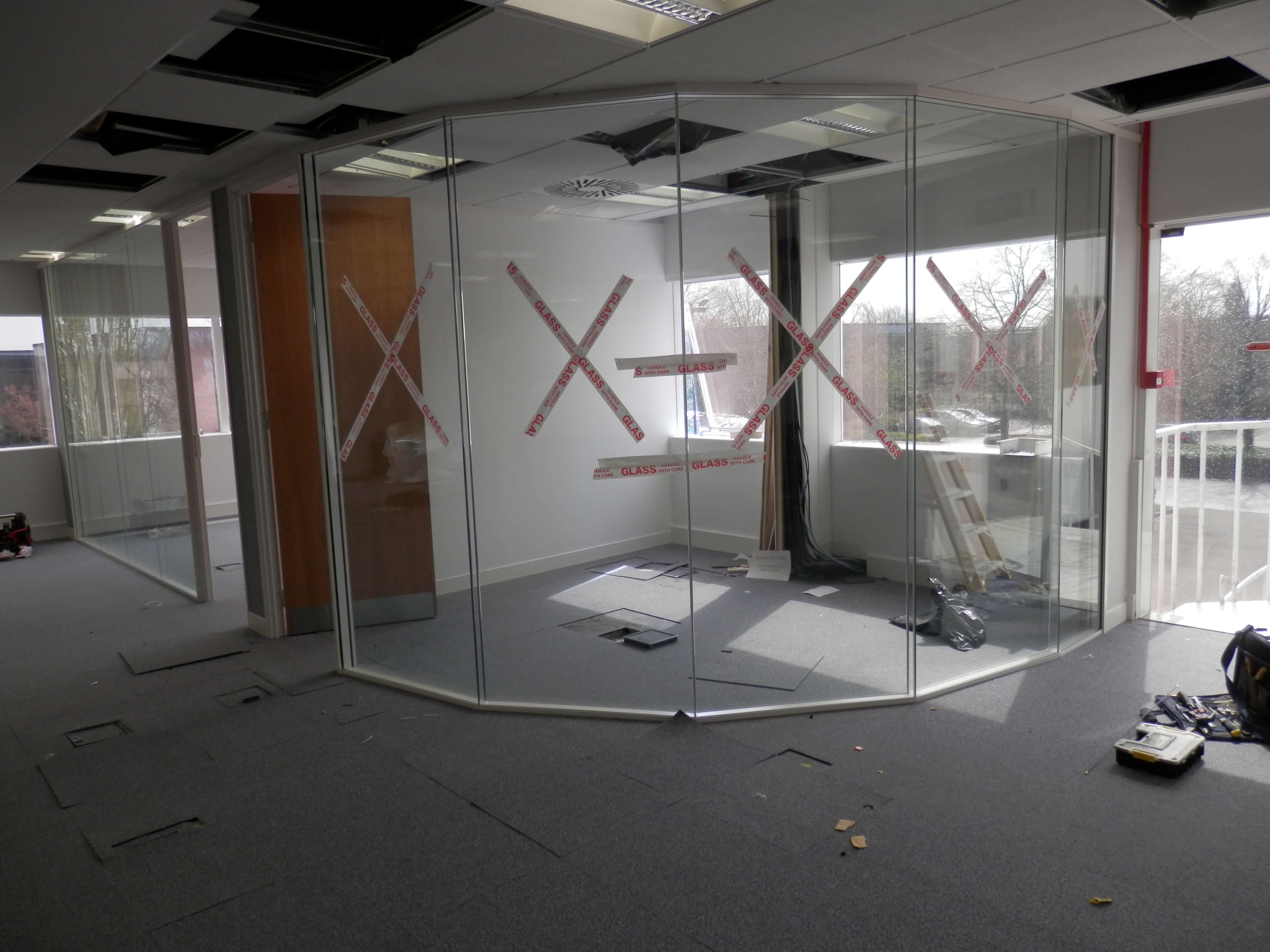 Faceted glass partitioning to form a small meeting room.